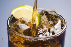 Refreshing glass of cola with lemon and ice. Isolated Stock Image