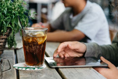 Refreshing glass of cola on wooden table in a bar while young is. Connected with tablet Royalty Free Stock Photos