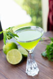 Refreshing glass of cold lime lemonade with mint on a wooden table in a restaurant with a creative decoration of mint leaves and f Royalty Free Stock Images