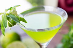 Refreshing glass of cold lime lemonade with mint on a wooden table in a restaurant with a creative decoration of mint leaves and f Stock Photos