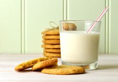 Refreshing glass of milk with a drinking straw, and delicious snack of homemade peanut butter cookies. With a tied stck of cookies Stock Photos