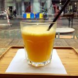 Orange Juice in Glass with Busy City Background. A refreshing glass of orange juice on a tray with a straw with a busy city undergoing construction in the royalty free stock photo