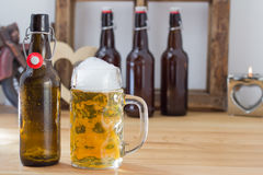 Refreshing glass tankard of frothy beer. Standing alongside a brown glass bottle on a wooden bar counter with copyspace and additional bottles visible behind Royalty Free Stock Photos