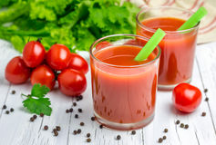 Refreshing glass of tomato juice. Healthy refreshing glass of tomato juice on the wooden table Stock Photos