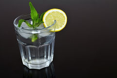 Refreshing glass of water with ice cubes flavored with lemon and mint. Summer refreshment. Royalty Free Stock Image