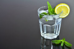 Refreshing glass of water with ice cubes flavored with lemon and mint. Summer refreshment. Royalty Free Stock Photo