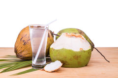 Refreshing green coconut fruit juice in glass on wooden table Stock Images
