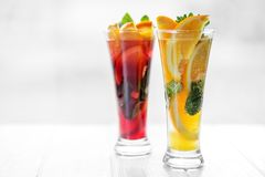 Refreshing healthy cocktails with mint and citrus and pomegranate on a white background. Concept for drinks, summer, heat, alcohol. Party and bar royalty free stock images