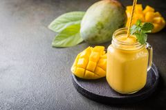 Healthy mango smoothie. Refreshing and healthy mango smoothie in a glass with fresh fruit over stone background with copy space stock images