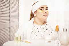 Resolute woman in bathrobe sitting in her beauty room. Refreshing her skin. Resolute woman in bathrobe sitting in her beauty room with golden patches under eyes stock photo
