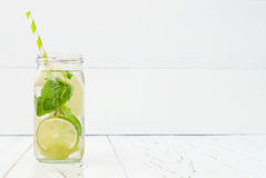 Refreshing homemade lime and mint cocktail over old vintage wooden table. Detox fruit infused flavored water. Clean eating Royalty Free Stock Images