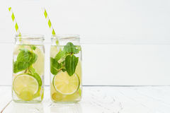 Refreshing homemade lime and mint cocktail over old vintage wooden table. Detox fruit infused flavored water. Clean eating. Copy space background stock images