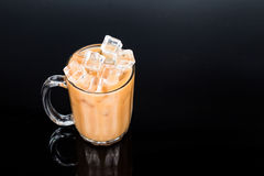 Refreshing ice cold tea with milk in transparent glass Stock Photos