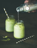 Refreshing iced coconut matcha latte and hand pouring milk Stock Image