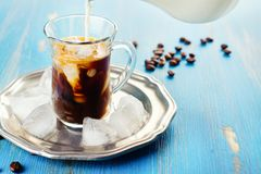 Refreshing iced coffee. With cream over blue summer background. Pouring milk into glass with coffee drink Stock Image