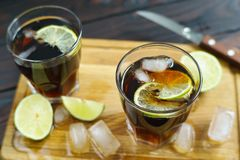 Refreshing iced longdrink Cuba Libre with rum and cola served on. Wooden board with lime slices and melting ice cubes stock photos
