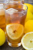 Refreshing iced tea with lemon on rustic wood Stock Images
