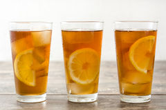 Refreshing iced tea with lemon on wood. Summer drink Stock Photos