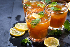 Refreshing iced tea with mint and lemon on dark background Stock Image