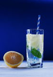 Refreshing lemon fresh mint. In a glass with a straw and lemon on a white table and blue background Royalty Free Stock Photography