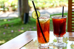 Refreshing lemon iced tea and black tea in the garden. Tasting the refreshing lemon iced tea and staring my children running around in the garden Royalty Free Stock Photography