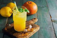 Refreshing lemon orange drink with ice and mint on a rustic blue table with backlighting. Summer cooling fruit drink close-up. Pla. Ce for text royalty free stock photo