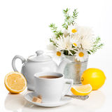 Refreshing Lemon Tea. Cup of refreshing lemon tea with teapot on white background with vase of spring flowers in background Royalty Free Stock Photos