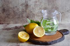 Refreshing lemonade in a beautiful decanter, lemons, fragrant sprigs of mint on the table. royalty free stock image