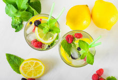 Refreshing lemonade with fresh mint. Delicious refreshing lemonade with fresh mint, Lemon, honey and ice decorated with raspberries, blueberries and blackberries Royalty Free Stock Photo
