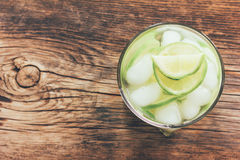 Refreshing lemonade with green lemon and ice close-up view. From above, toning photo Royalty Free Stock Photos