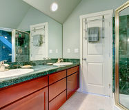 Refreshing light green bathroom with bright brown cabinets Stock Photos