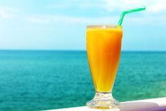 Refreshing looking orange juice by the sea Stock Photo