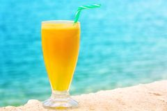 Refreshing looking orange juice by the sea Royalty Free Stock Images