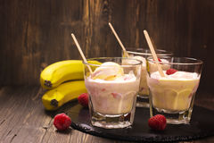 Refreshing milk cocktail with ice cream scoops, raspberry and banana. Over vintage table. Selective focus Royalty Free Stock Photos