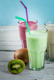 Refreshing milkshakes or smoothies. White banana, green apple and kiwi and berries; with fresh fruits. On a white wooden table, copy space royalty free stock photos