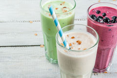 Refreshing milkshakes or smoothies. White banana, green apple and kiwi and berries. On a white wooden table, close view, copy space royalty free stock images