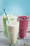 Refreshing milkshakes or smoothies. White banana, green apple and kiwi and berries. On a white wooden table, copy space stock images