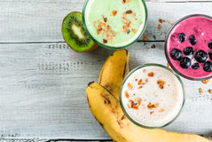 Refreshing milkshakes or smoothies. White banana, green apple and kiwi and berries. On a white wooden table, copy space, top view royalty free stock photo