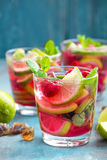 Refreshing mint cocktail mojito with rum, lime and raspberry, cold drink or beverage. Refreshing mint cocktail mojito with rum, lime and raspberry, red cold Royalty Free Stock Images