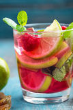 Refreshing mint cocktail mojito with rum, lime and raspberry, cold drink or beverage. Refreshing mint cocktail mojito with rum, lime and raspberry, red cold Stock Images