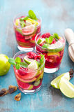 Refreshing mint cocktail mojito with rum, lime and raspberry, cold drink or beverage. Refreshing mint cocktail mojito with rum, lime and raspberry, red cold Stock Photo