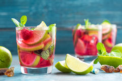 Refreshing mint cocktail mojito with rum, lime and raspberry, cold drink or beverage. Refreshing mint cocktail mojito with rum, lime and raspberry, red cold Royalty Free Stock Photo