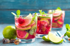 Refreshing mint cocktail mojito with rum, lime and raspberry, cold drink or beverage. Refreshing mint cocktail mojito with rum, lime and raspberry, red cold Royalty Free Stock Photos