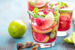 Refreshing mint cocktail mojito with rum, lime and raspberry, cold drink or beverage Royalty Free Stock Image