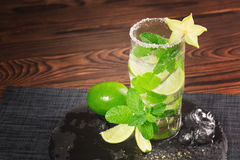 A refreshing mojito cocktail on a wooden background. Lime mojito with rum, mint and carambola. Glass of alcohol drink. Copy space. stock images