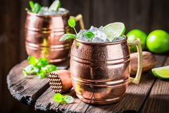 Refreshing Mojito with lime and mint. On wooden table Stock Photography