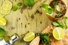 Refreshing moscow mule cocktail. In copper mug with mint and lime on wet wooden table. Space for text Royalty Free Stock Photography