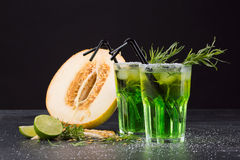 Refreshing non-alcohol drinks. Cut melon and green cocktails on a black background. Sweet drinks with liquor, lime and tarragon. stock photography