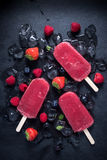 Refreshing popsicle on ice cubes and fruits. Food background stock photos