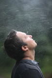 Refreshing rain. Drops of rain fall on the man's face royalty free stock photos